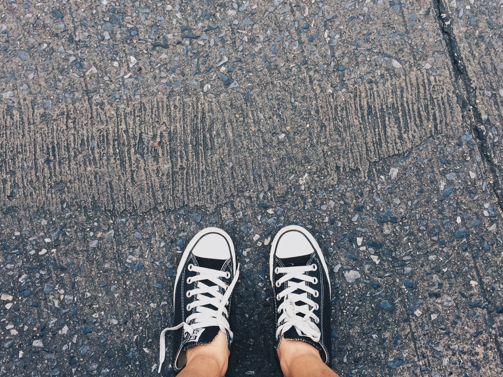 person wearing pair of black and white converse all star low sneakers